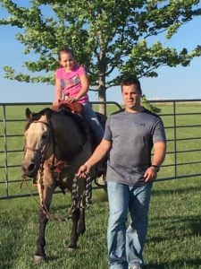 Ben Peterson and daughter on farm